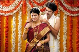 El novio poniéndole el collar Mangalsutra a la novia